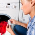 1199331-a-young-housewife-with-washing-machine-and-clothes-washing-day